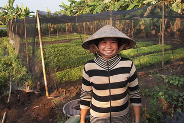 A loan recipient in front of her environmentally friendly net greenhouse.