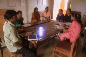 Students exhibit one of the many solar-powered LED lights they built, wired, and sold to villagers as part of the IBT program.