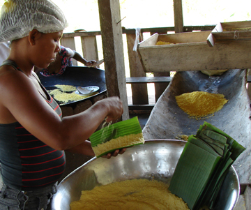A co-op member coats palm leaves with a layer of cassava to make cassava chips. (photo by Stephanie Wolcott)